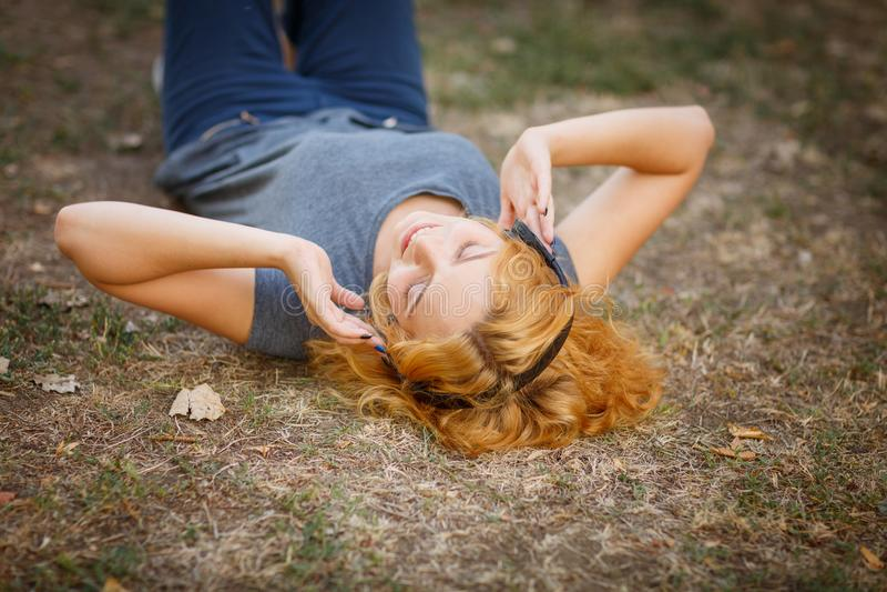 Fille calme de gingembre dans des écouteurs détendant sur un fond d'herbe Concept de temps gratuit photos stock