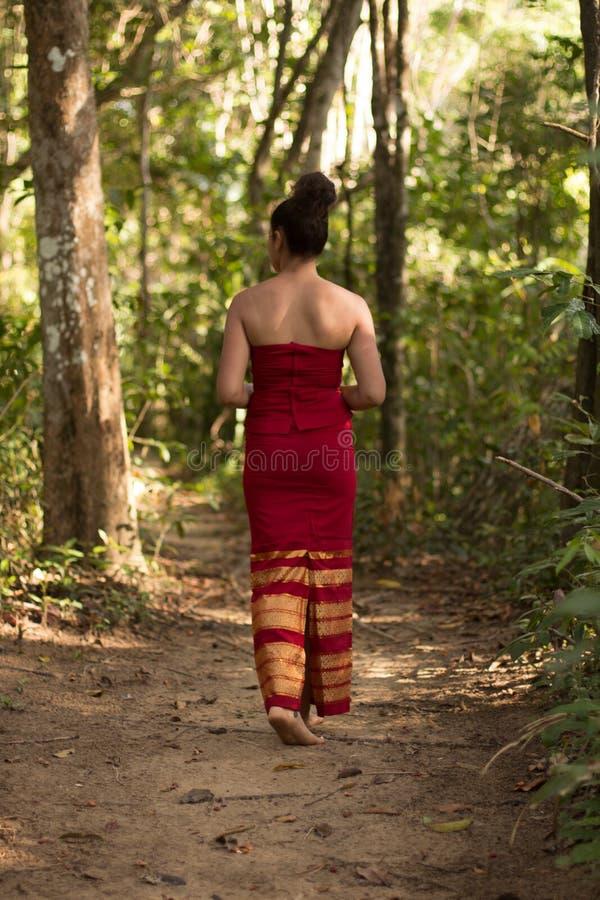 Fille cambodgienne dans la robe de Khmer marchant un chemin par la jungle photos libres de droits