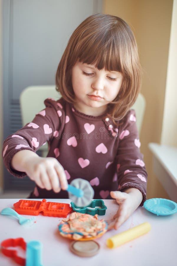 Fille caucasienne blanche d'élève du cours préparatoire jouant le playdough de pâte à modeler à l'intérieur à la maison photographie stock