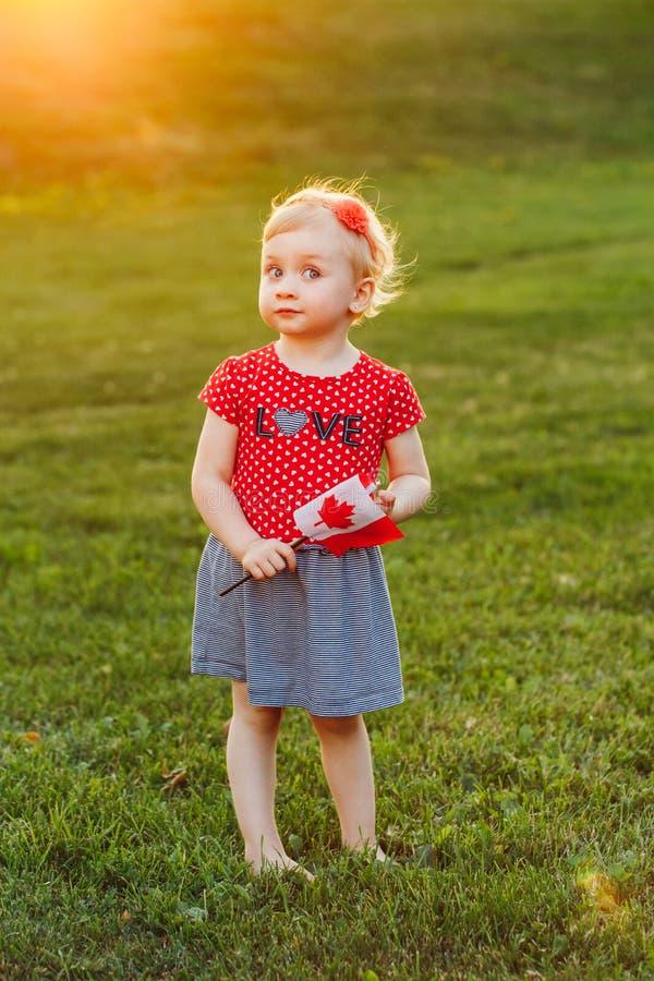 Fille caucasienne blonde d'enfant en bas âge de bébé tenant le drapeau canadien de ondulation images libres de droits