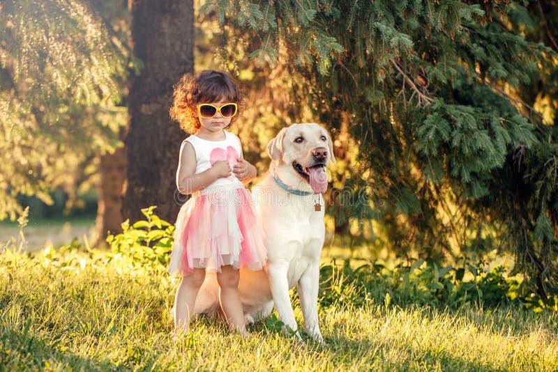 Fille caucasienne d'enfant dans des lunettes de soleil marchant le chien en parc photographie stock libre de droits