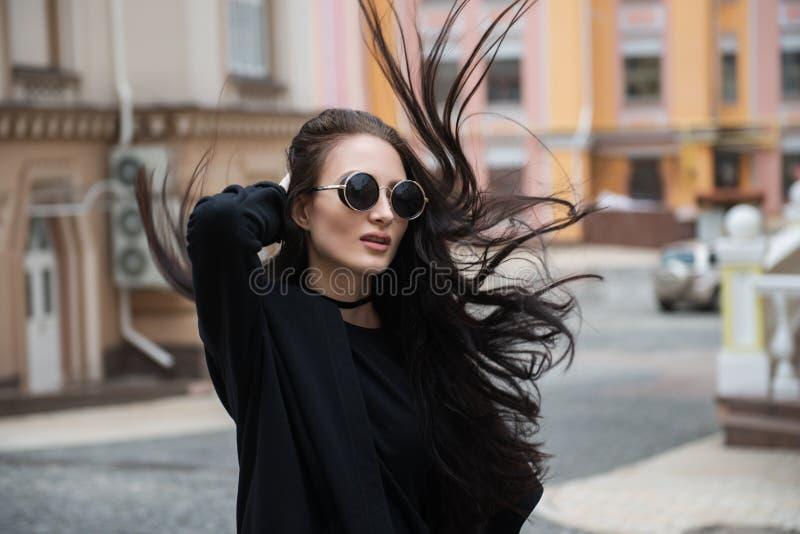 Fille caucasienne de belle brune élégante jeune dans des vêtements noirs sur la rue dans des lunettes de soleil images stock
