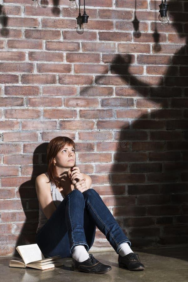 Fille caucasienne s'asseyant sur le plancher lisant une horreur ou un livre effrayant de thriller Éclairage dramatique avec des y image stock