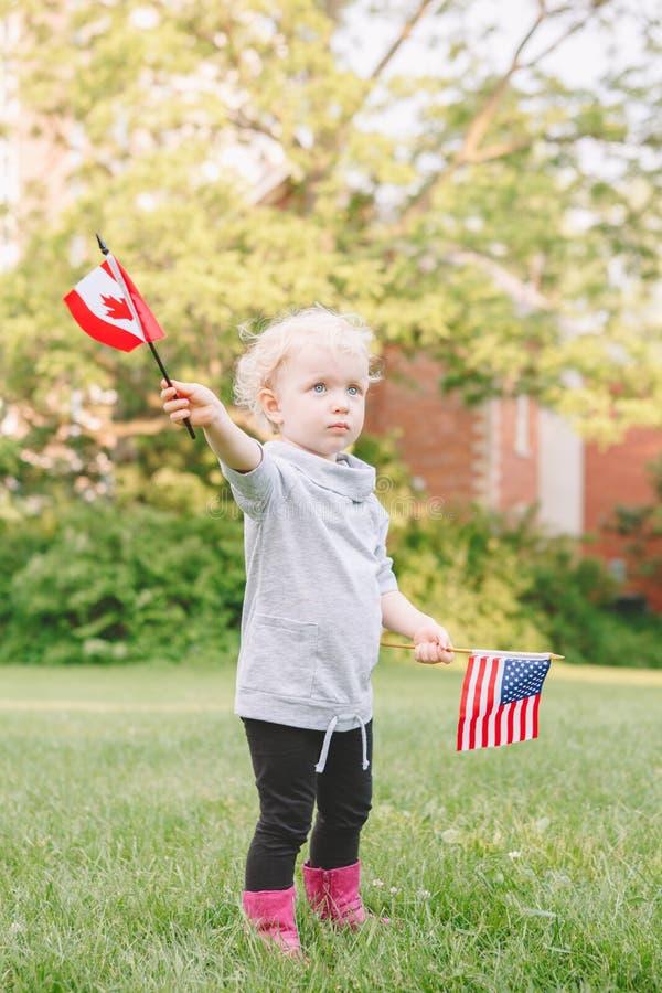 Fille caucasienne tenant onduler le drapeau américain et canadien dans parc le 4 juillet de célébration extérieur images libres de droits