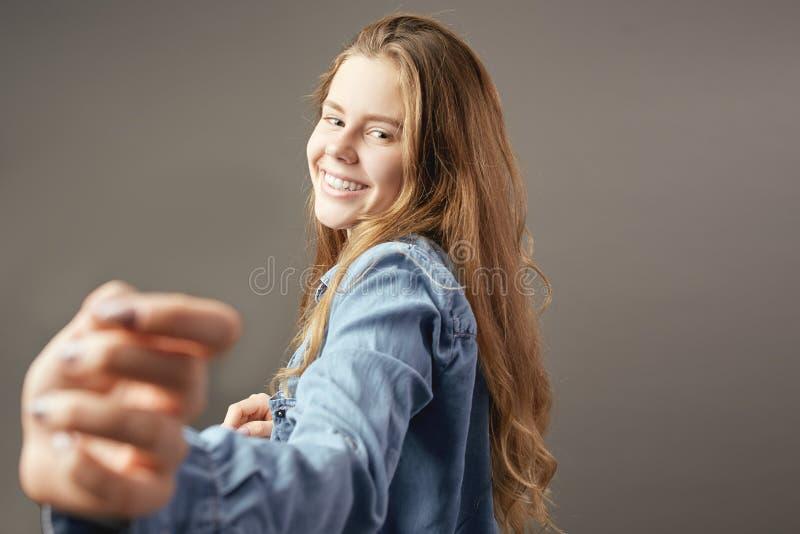 Fille châtain habillée dans des sourires de chemise de jeans sur un fond gris images stock