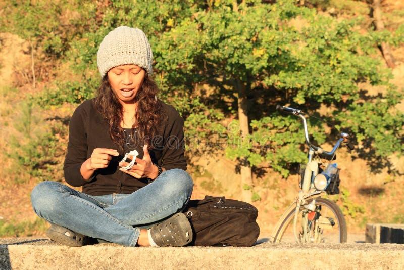 Fille chanteuse avec le vélo derrière image libre de droits