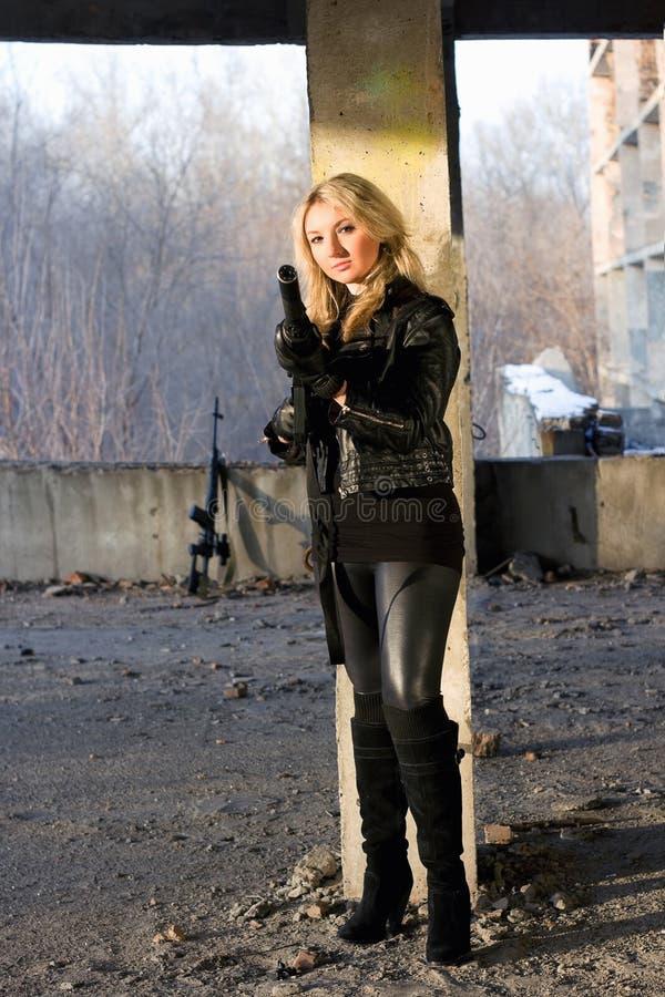 Jeune femme chaude avec une arme à feu photo stock