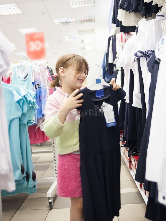 Fille chez le magasin d'habillement du ` s des enfants photographie stock