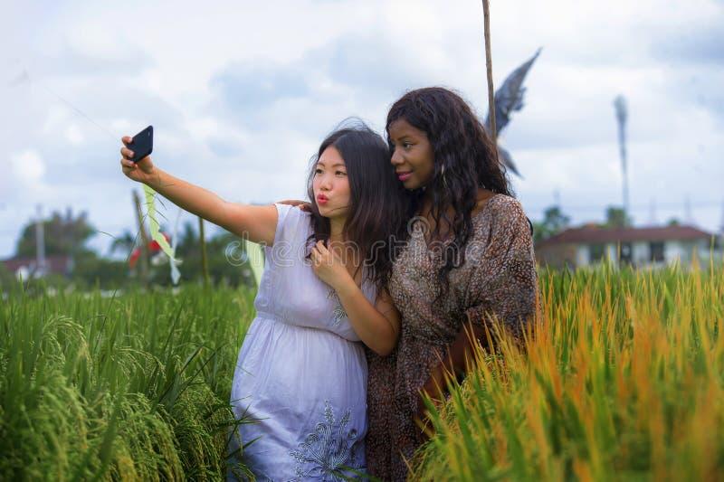 Fille chinoise asiatique d'appartenance ethnique mélangée et femme américaine d'africain noir prenant à amies le selfie avec le t photo libre de droits
