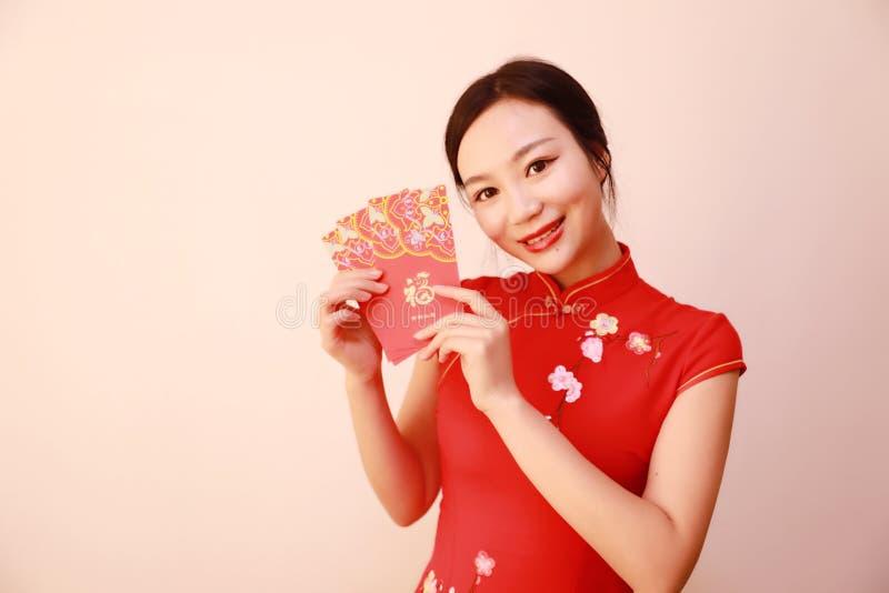 Fille chinoise dans le cheongsam traditionnel de robe tenant la prise rouge de femme de paquets avec l'argent chanceux image stock