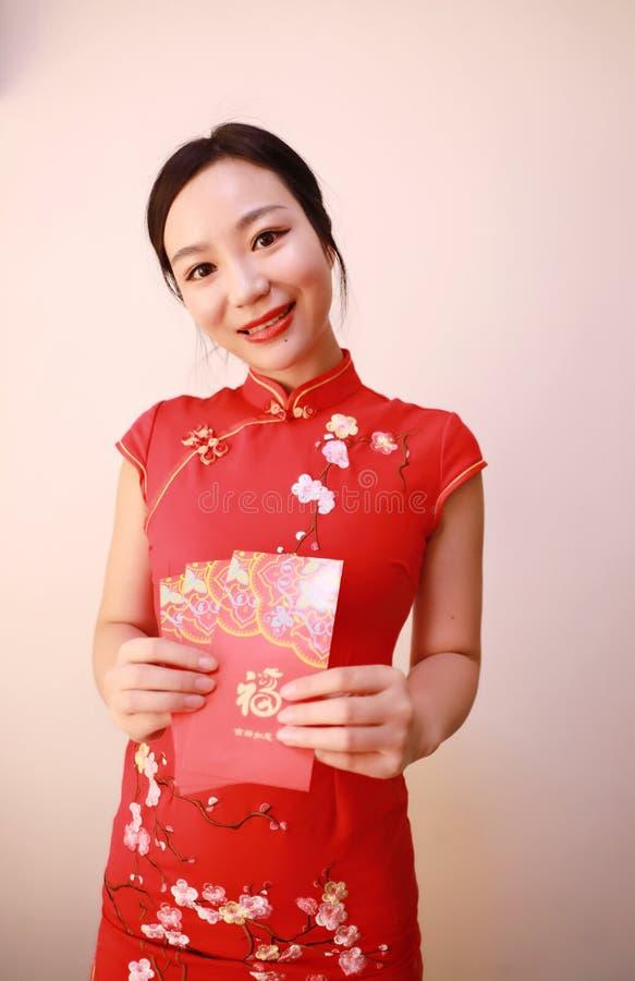 Fille chinoise dans le cheongsam traditionnel de robe tenant la prise rouge de femme de paquets avec l'argent chanceux image libre de droits