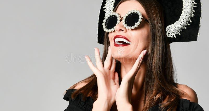 Fille choquée élégante, dans la robe noire avec des lunettes de soleil images stock