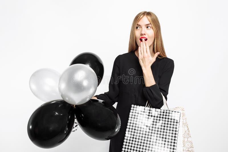 Fille choquée élégante, dans la robe noire, avec des paniers et le bla images stock