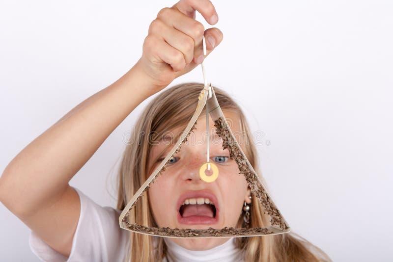 Fille choquée jugeant un piège de mite plein des mites emprisonnées de nourriture image stock