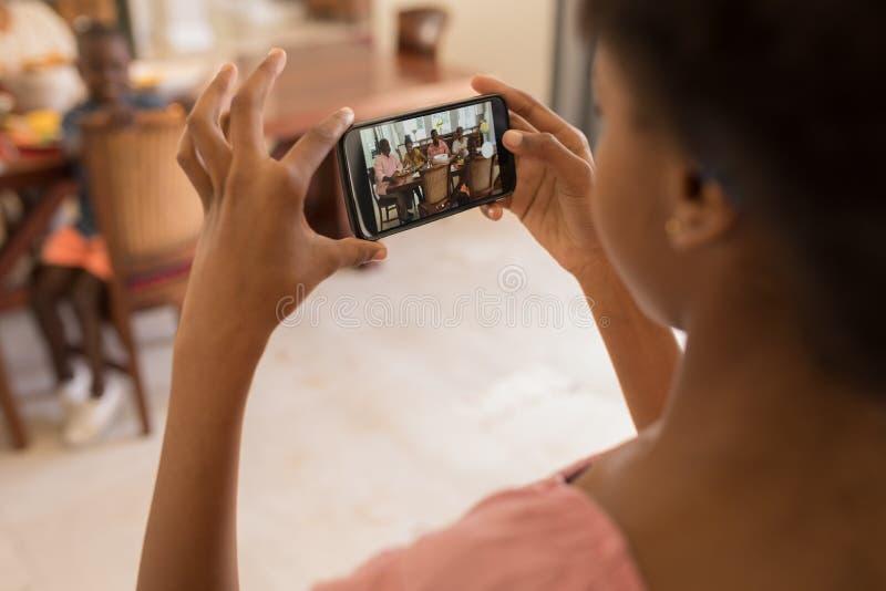 Fille cliquant sur des photos de famille avec le téléphone portable sur la table de salle à manger images stock