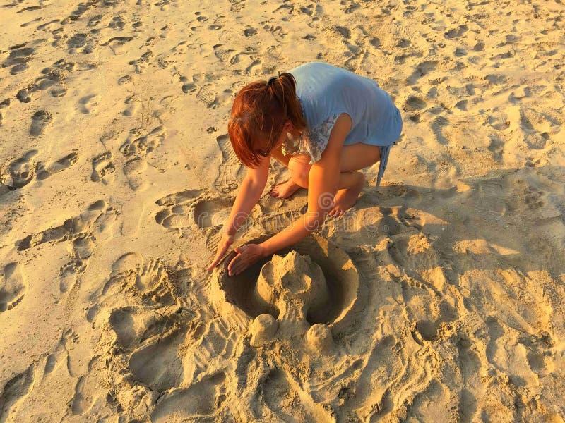 Fille construisant un château sur la plage photo libre de droits