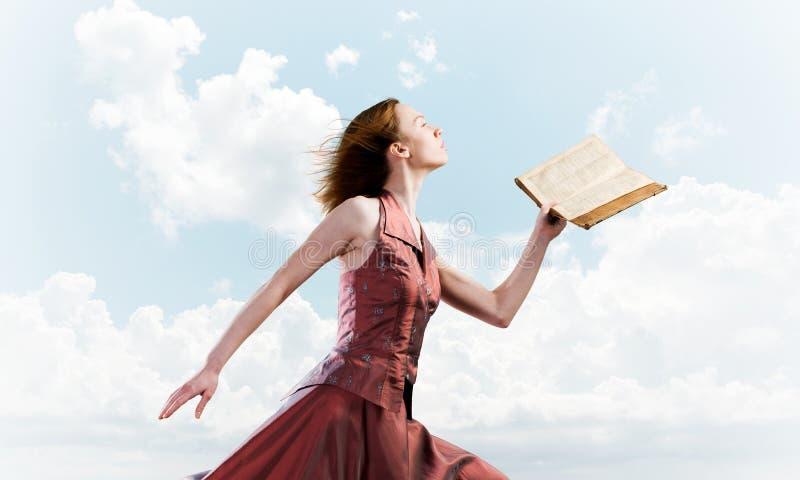 Fille contre le ciel nuageux avec le livre ouvert dans la paume comme id?e pour la connaissance photographie stock libre de droits