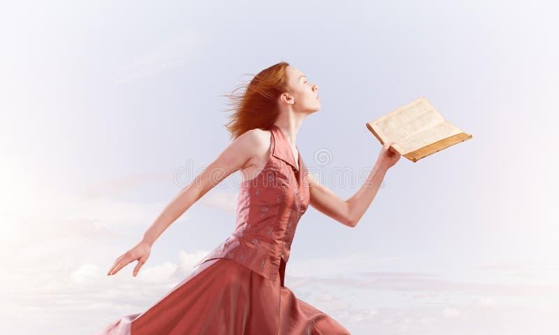 Fille contre le ciel nuageux avec le livre ouvert dans la paume comme id?e pour la connaissance image libre de droits