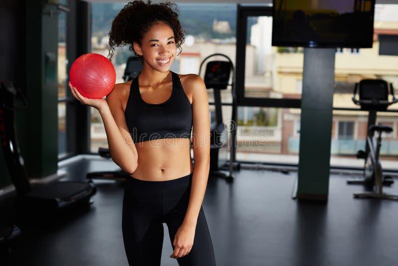 Fille convenable de jeunes avec modifier la tonalité la boule au centre de fitness photos libres de droits