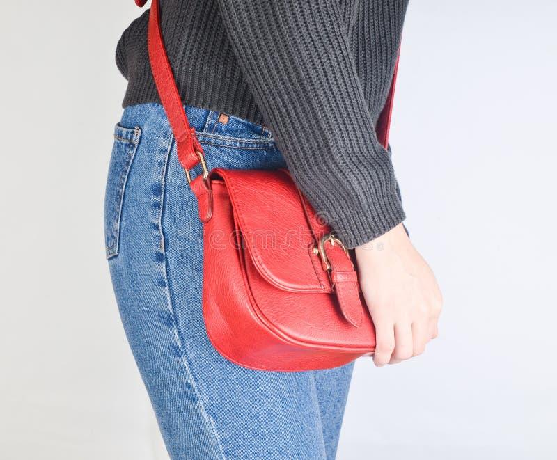 Fille convenable de jeunes dans les jeans et le chandail tenant un sac en cuir rouge avec ses mains sur un fond blanc image stock