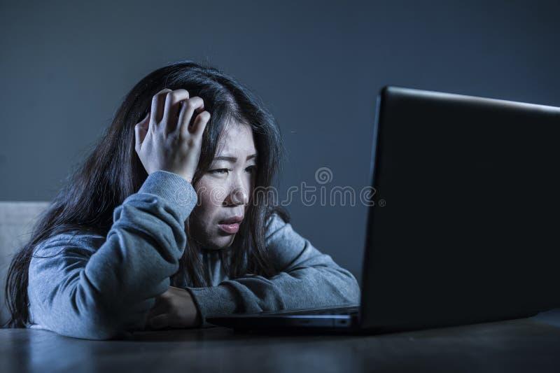 Fille coréenne asiatique inquiétée d'étudiant semblant étude diminuée et désespérée avec l'ordinateur portable dans l'effort pour image stock