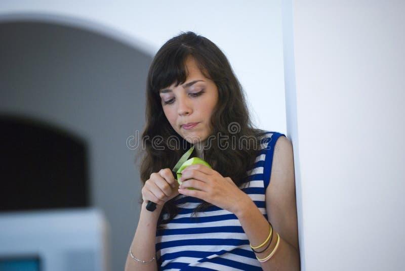 Fille coupant en tranches une pomme images stock