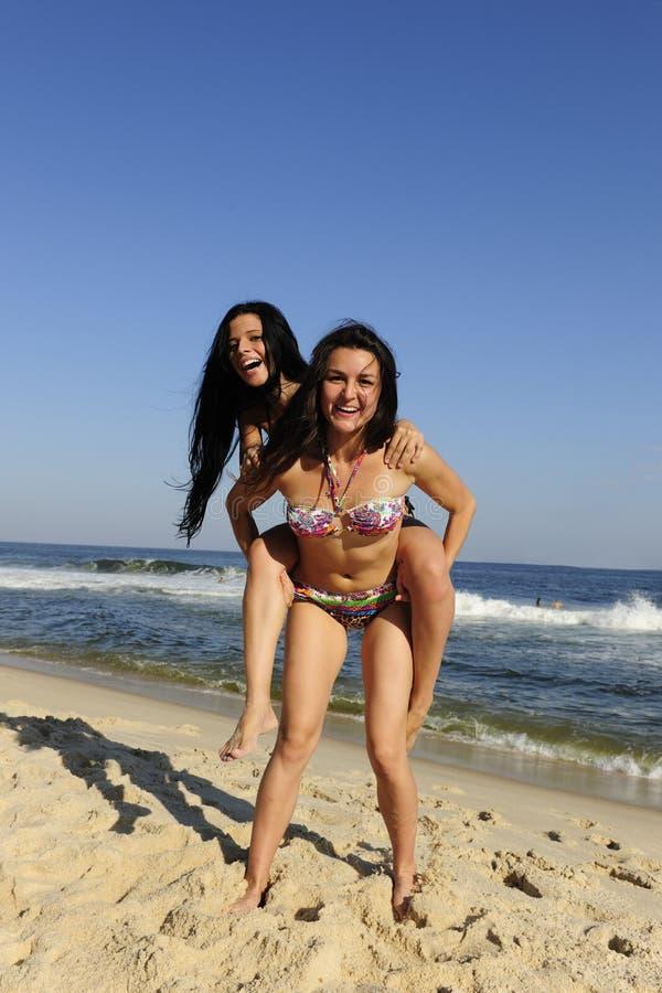 Fille couvrant son ami sur la plage images stock