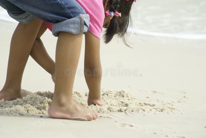 Fille creusant sur la plage sablonneuse photo libre de droits