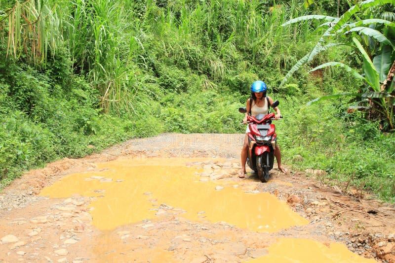 Fille croisant l'étang boueux sur la motocyclette photographie stock libre de droits