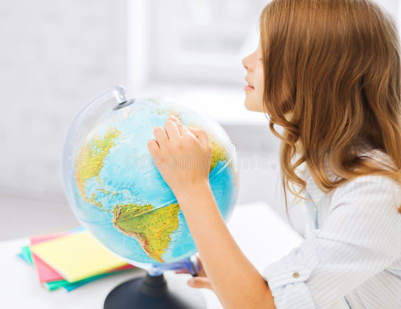 Fille curieuse d'étudiant avec le globe à l'école photographie stock