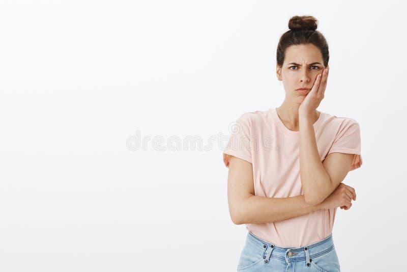Fille déçue réagissant à la mauvaise nouvelle Portrait de femme mignonne sombre et boudante avec le petit pain malpropre, touchan photos stock