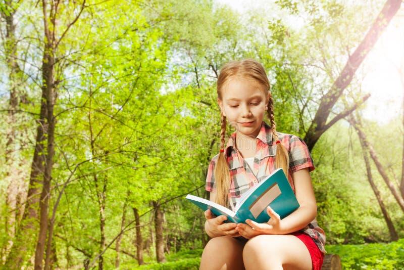 Fille décontractée adorable lisant un livre extérieur photo libre de droits