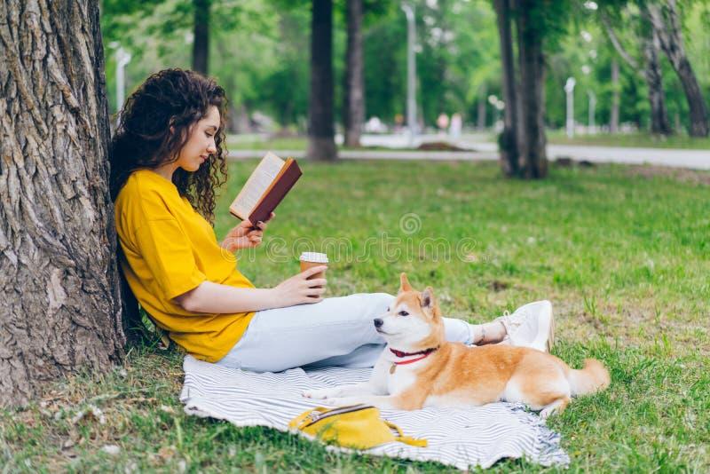 Fille décontractée tenant le café et le livre de lecture en parc se reposant sur la pelouse avec le chien photo libre de droits