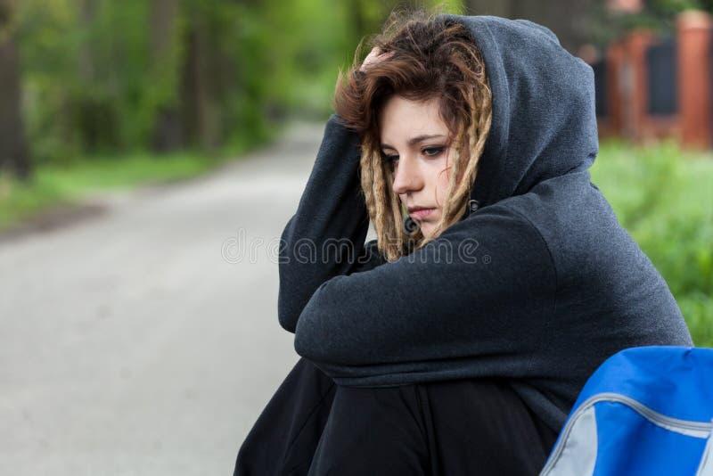 Fille déprimée dans le capot s'asseyant sur la route photographie stock libre de droits