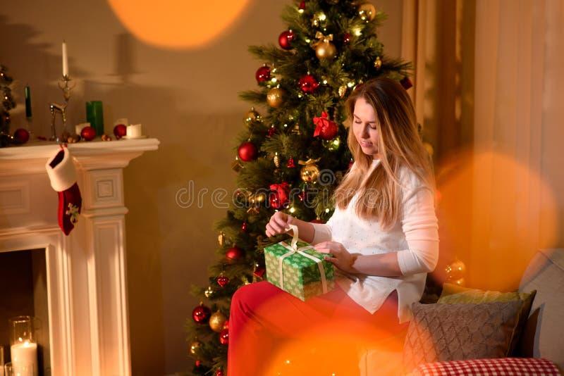 Fille déroulant l'arbre de vacances de cadeau de Noël photographie stock libre de droits