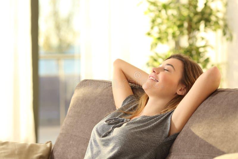 Fille détendant sur un sofa à la maison images stock