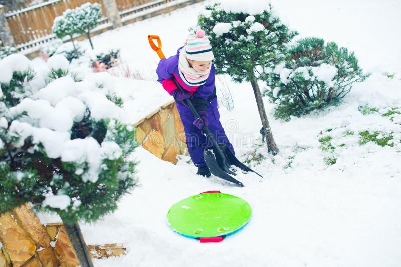 Fille d'âge scolaire travaillant avec la pelle dans la cour neigeuse d'hiver photo stock