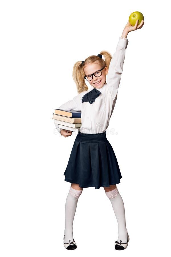 Fille d'école, élève heureux dans l'uniforme avec des livres soulevant Apple images libres de droits