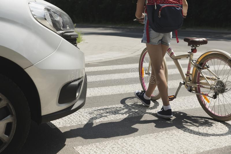 Fille d'école d'adolescent avec la promenade de sac à dos et de vélo dans le passage pour piétons photographie stock