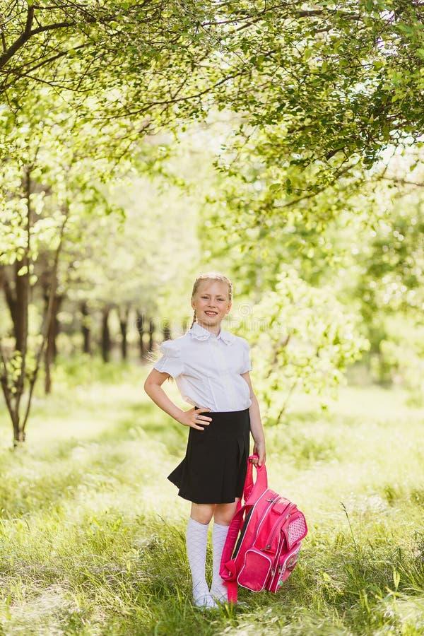 Fille d'école primaire tenant le sac à dos d'école dehors photo stock