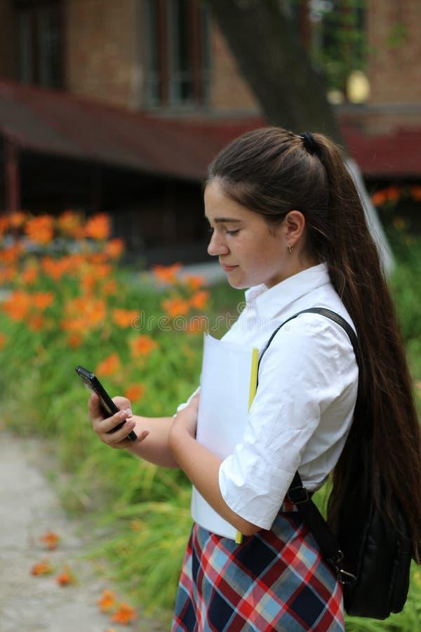 Fille d'écolière avec de longs cheveux dans l'uniforme scolaire parlant au téléphone photos libres de droits