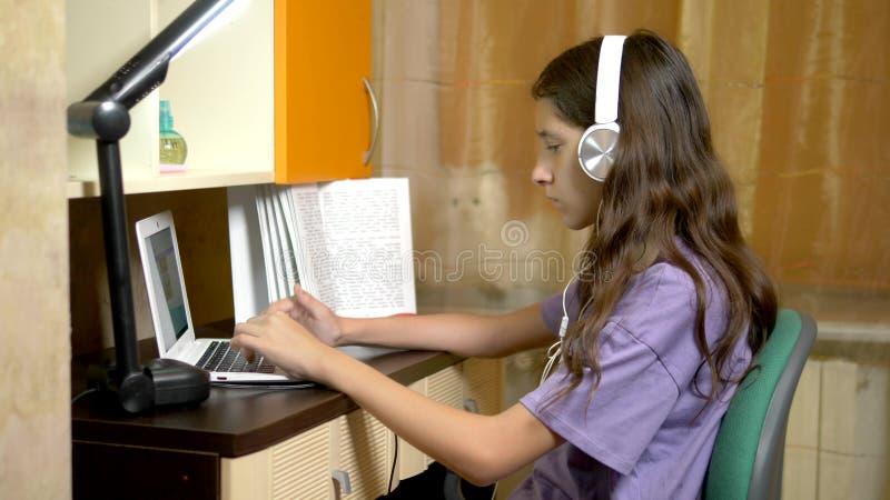 Fille d'étudiant apprenant sur la ligne avec un ordinateur portable blanc se reposant à une table dans sa pièce de l'adolescence  photographie stock libre de droits