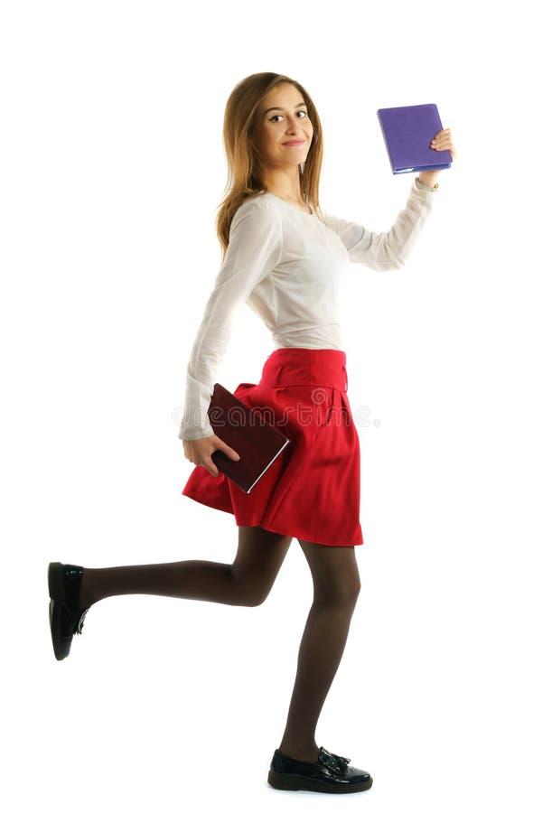 Fille d'étudiant courant avec des carnets d'isolement sur le fond blanc image stock