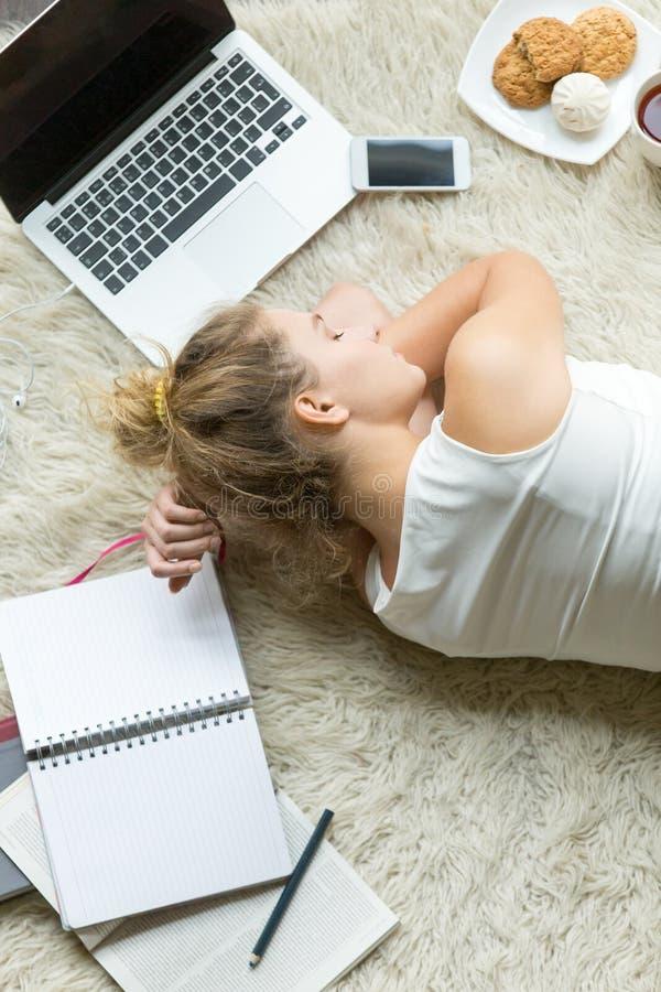 Fille d'étudiant dormant au lieu de l'étude à la maison image stock