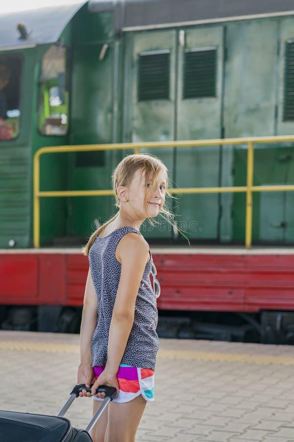 Fille d'adolescent à la station de train près de la locomotive fille tirant une grande valise sur la plate-forme Photo verticale image stock