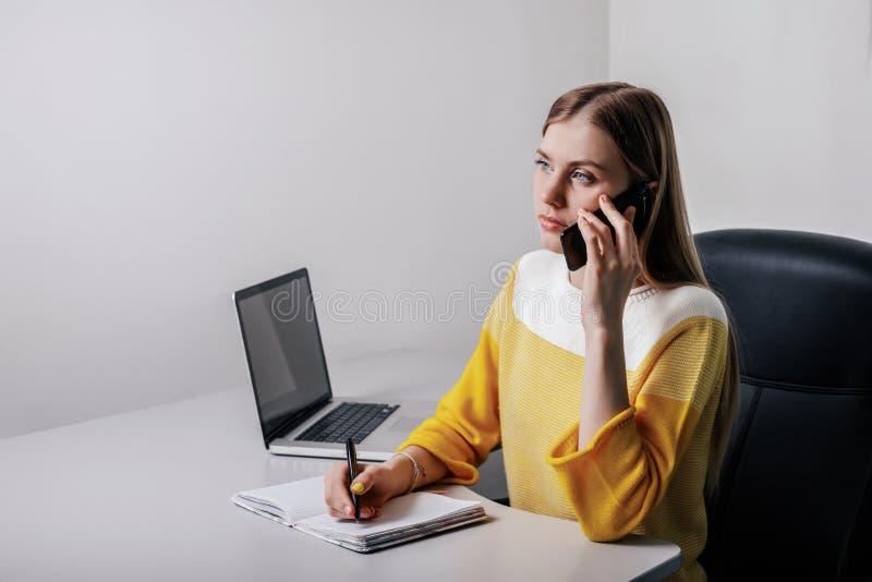 Fille d'adolescent écrivant sur un bloc-notes et téléphonant tout en se reposant dans un bureau photo libre de droits