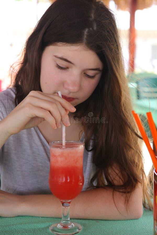 Fille d'adolescent avec la longue secousse brune de pastèque de boissons de cheveux en café image stock