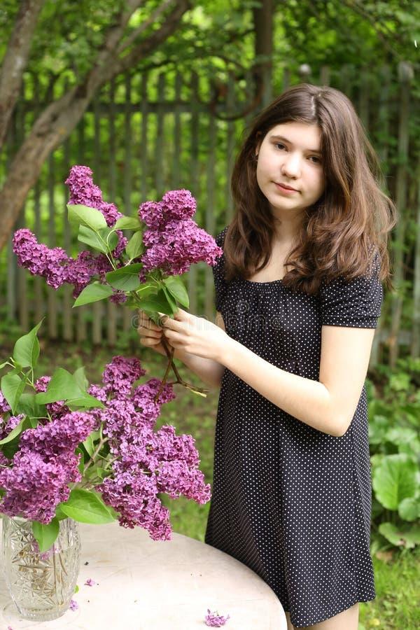 Fille d'adolescent avec la robe de point de polka avec les fleurs lilas photographie stock libre de droits