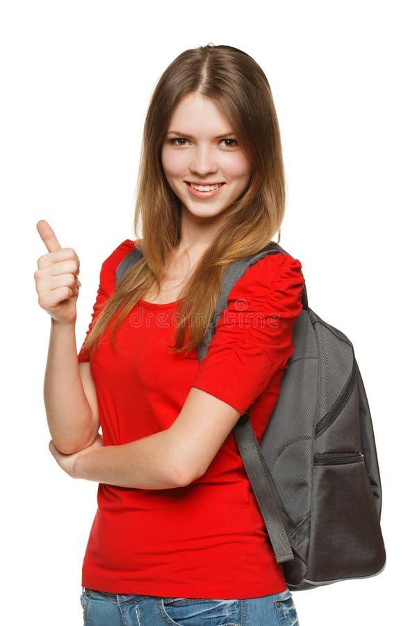Fille d'adolescent avec le sac à dos affichant le pouce vers le haut image libre de droits