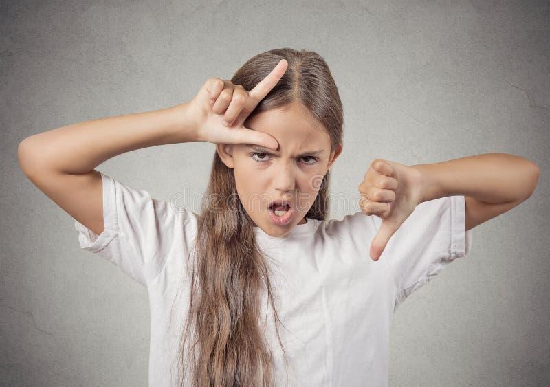 Fille d'adolescent montrant le signe de perdant donnant des pouces vers le bas images libres de droits